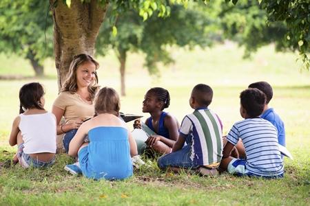 Une jeune enseigne a des enfants assis devant elle sous un arbre