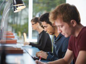 3 jeunes assis à une table de travail
