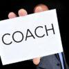 Une main présente un carton blanc où il est inscrit coach de carrière